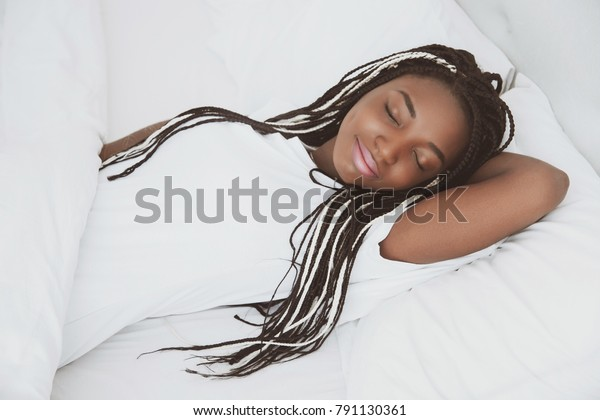 A beautiful African woman lies and sleeps in bed, in a white bedroom. Good morning, vacation at home. The girl is wearing a T-shirt, pigtails on her head. Healthy sleep. Nigeria, Africa.