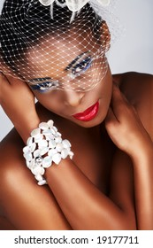 beautiful African woman with net over her face and pearl bracelet