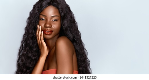 Beautiful African woman portrait. Brunette curly haired young model with dark skin touching her chin and posing against grey background . Web banner witch copy space.