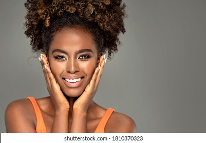 Beautiful african woman smiling and looking at camera with joy.  Beauty afro american girl with curly hair smiling, posing on gray studio background.