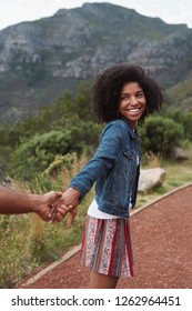 Beautiful african woman smiling and pulling boyfriend partner along, holiday vacation explore wanderlust