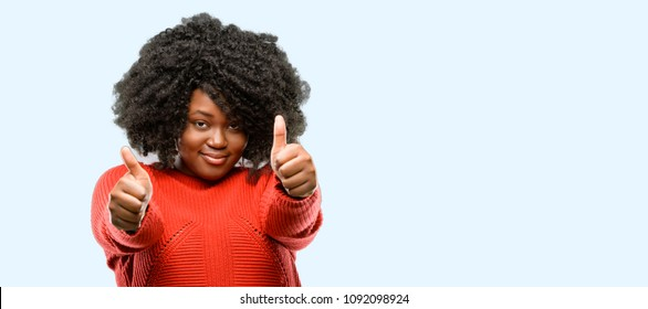 Beautiful african woman stand happy and positive with thumbs up approving with a big smile expressing okay gesture, blue background