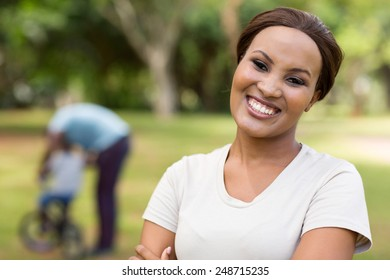 beautiful african woman standing in front of family outdoors