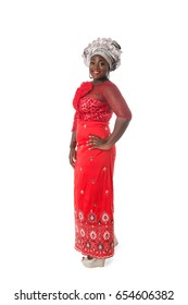 Beautiful African woman standing in traditional red costume on white background.Studio shot