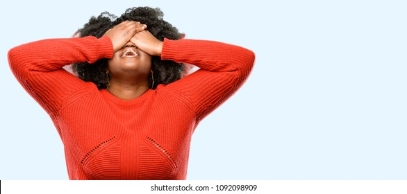 Beautiful african woman stressful keeping hands on head, tired and frustrated, blue background
