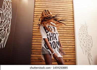 Beautiful african woman in stylish casual clothes posing against angel wings wall. She moving her hair dreadlocks.