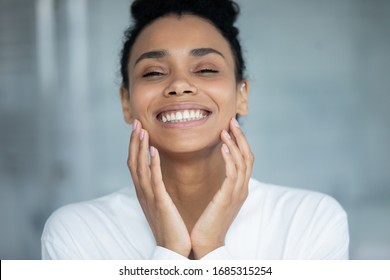 Beautiful african woman touch face enjoy ideal flawless fresh smooth facial skin close up portrait. Laser skin resurfacing, glycolic acid peel, anti-ageing skincare procedures and cosmetics ad concept