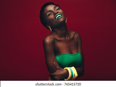 Beautiful african woman with vivid makeup. Beauty portrait of sensual model with colorful makeup on red background.