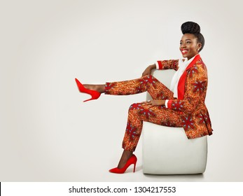 Beautiful African woman wearing an African print suit sitting with her leg propped up on a chair smiling broadly