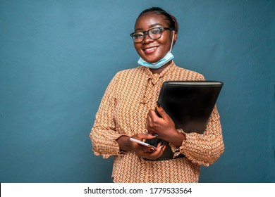 Beautiful African woman wearing spectacles, smiling, wearing surgical face mask for protection in covid-19 pandemic and holding a black case for documents and laptop,isolated on a blue background