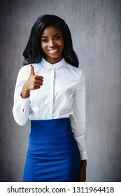 Beautiful African Woman In White Shirt And Blue Skirt Does An Ok Sign With Thumbs Up. Portrait Of African Businesswoman Smiling And Showing Thumb Up.