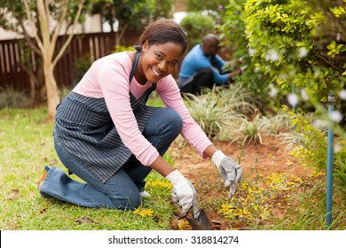 beautiful african woman working in the garden with her husband