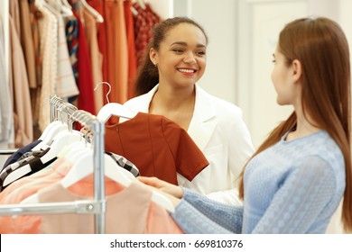 Beautiful African woman working at her fashion store helping her female customer choosing clothes profession owner businesswoman people communication sales seller retail manager helpful assistance