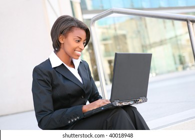 Beautiful African woman working on laptop at office building