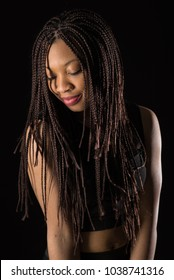Beautiful African young woman close up portrait with braids against dark background.