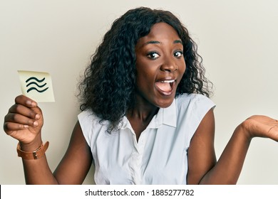 Beautiful african young woman holding paper with aquarius zodiac sign celebrating achievement with happy smile and winner expression with raised hand