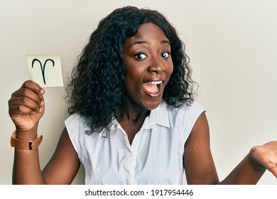 Beautiful african young woman holding paper with aries zodiac sign celebrating achievement with happy smile and winner expression with raised hand