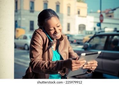 beautiful african young woman using smart phone in the city