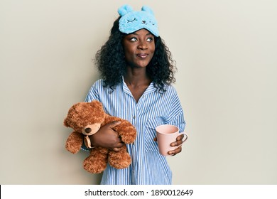 Beautiful african young woman wearing pajama, holding teddy bear and drinking coffee smiling looking to the side and staring away thinking.