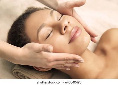 Beautiful African-American girl having massage in spa salon