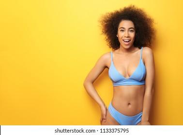Beautiful African-American woman in bikini on color background