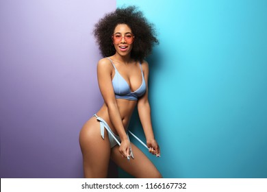 Beautiful African-American woman in bikini and with sunglasses on color background