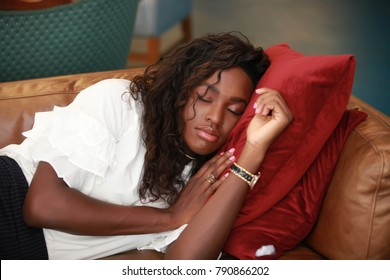 Beautiful African-American woman keeping head on red pillows while taking nap on comfortable sofa.