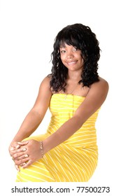 A beautiful African-American woman in a long yellow dress and dark black hair sitting on a chair, for white background.