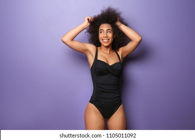 Beautiful African-American woman in swimming suit on color background