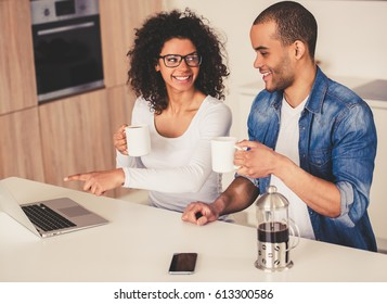 Beautiful Afro American couple is drinking coffee, talking and smiling while using a laptop in kitchen