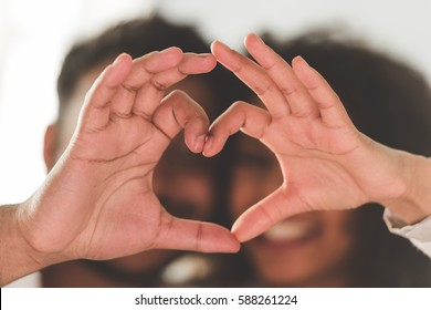 Beautiful Afro American couple is making a heart of their hands and smiling. Hands in focus