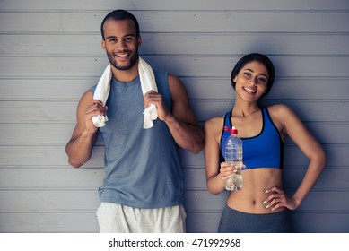 Beautiful Afro American couple in sports clothes is holding a bottle of water and a towel, looking at camera and smiling, standing in front of gray wall