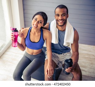 Beautiful Afro American couple in sports clothes is holding a bottles of water, looking at camera and smiling while resting after workout