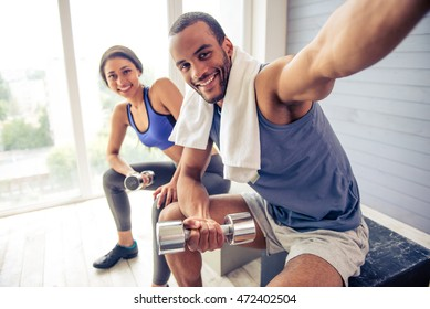 Beautiful Afro American couple in sports clothes is making selfie, holding dumbbells, looking at camera and smiling while resting after workout