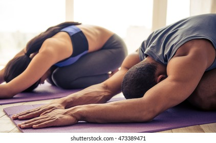 Beautiful Afro American couple in sports clothes is stretching on yoga mat while working out at home