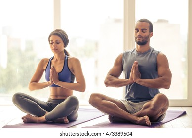 Beautiful Afro American couple in sports clothes is meditating sitting in lotus position on mat while doing yoga