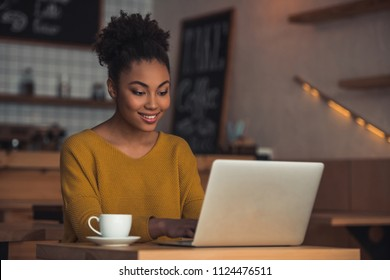 Beautiful Afro American girl in casual clothes is using a laptop and smiling while sitting in cafe