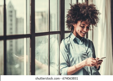 Beautiful Afro American girl in casual clothes is using a smart phone and smiling while standing near the window