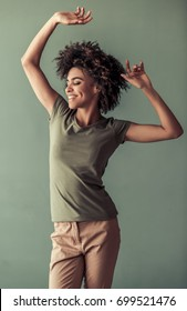 Beautiful Afro American girl in casual clothes is dancing and smiling, on gray background