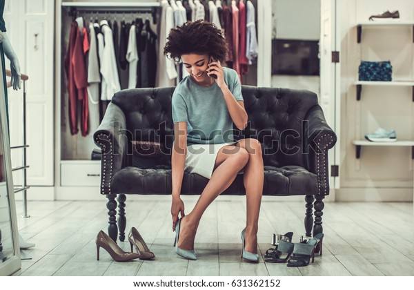Beautiful Afro American girl is choosing high-heeled shoes, talking on the mobile phone and smiling while doing shopping in female boutique