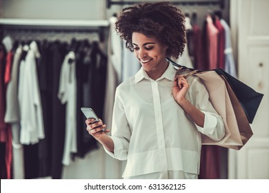 Beautiful Afro American girl is holding shopping bags, using a smart phone and smiling while doing shopping in female boutique