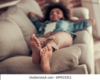 Beautiful Afro American girl is napping on couch at home, feet in focus