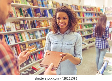 Beautiful afro american girl is smiling while buying book at the bookshop using a credit card