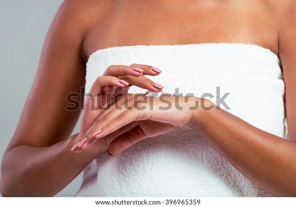 Beautiful Afro American girl with a towel on her head is applying cream on her hand, on a gray background, close up