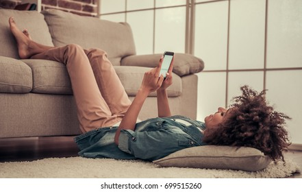 Beautiful Afro American girl is using a smart phone while lying on the floor, her legs on couch