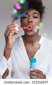 Beautiful afro american woman blowing bubbles against white wall