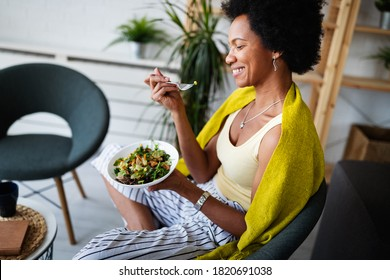 Beautiful afro american woman eating vegetable salad at home. - Shutterstock ID 1820691038