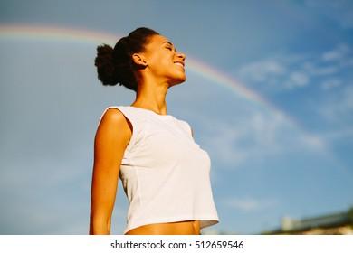 Beautiful afro american woman enjoying rainbow in summer day