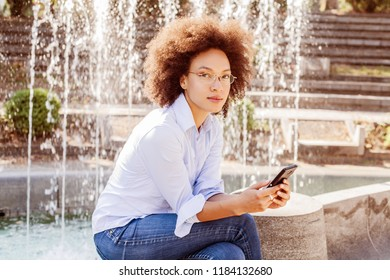 Beautiful Afro American Young Woman With Glasses Using Smartphone. Outdoor Portrait Of Mixed Race Student, Casual Wear , Looking At The Camera