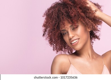Beautiful afro girl beauty portrait. Pink background. Young woman smiling to the camera.